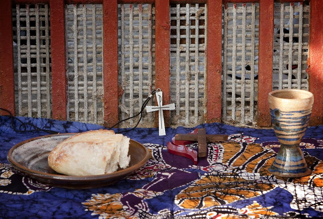 The elements of Holy Communion are laid out against the Mexico side of the border fence between Tijuana and San Diego during a cross-border service at El Faro park in Tijuana, Mexico. Photo by Mike DuBose, United Methodist Communications.