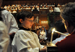 An acolyte lights a candle during a special service at St. Paul's United Methodist Church. Children flll all the roles for the service on the third Sunday of Advent.
