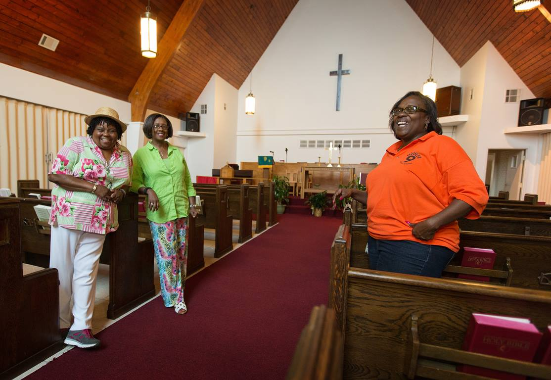 Church members (from left) Burnetta D. Fauria, Angelique White-Williams and Andrea Sanchez-Reese show the restored sanctuary at Hartzell United Methodist Church in New Orleans' Lower 9th Ward. Among the items dedicated last year were new imprinted hymnals from Cokesbury Cares. Photo by Mike DuBose, UMNS.
