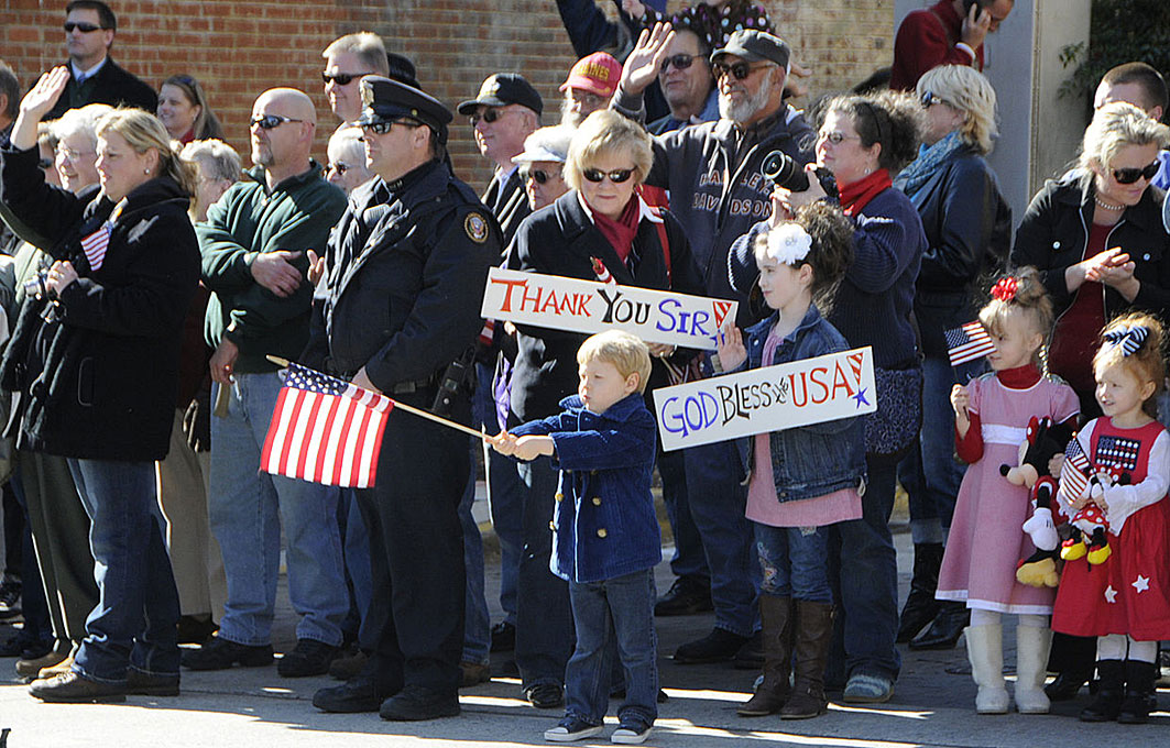 An American boy waves a U.S. flag during a Veterans Day parade. Public domain photograph from defenseimagery.mil.