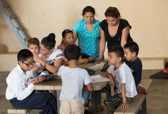 """Mothers and children gather around a table in the playroom at the """"Door of Hope"""" Salvation Army shelter in Tijuana. Photo by Mike DuBose, UMNS."""