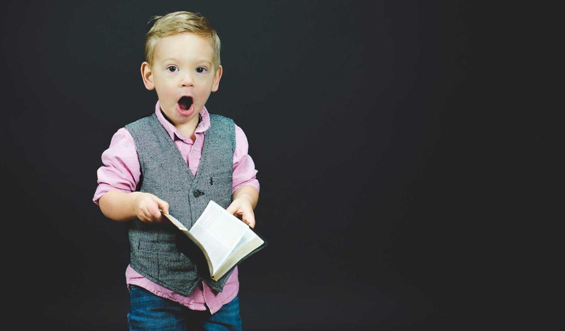 little boy pink shirt holding bible