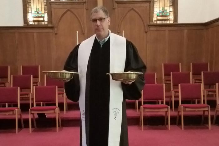 While the Rev. Richard Burstall promotes the availability of online giving at Michelson Memorial United Methodist Church, receiving gifts in the traditional plates is still a part of each service. Photo courtesy of the Rev. Richard Burstall.