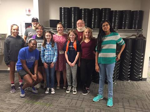 Students from Faith Westwood UMC IMPACT afterschool program for middle schoolers in Nebraska have just finished unloading 500 buckets and lids donated to the church. Behind them are just a small number of those buckets. PHOTO: VIKKI O'HARA
