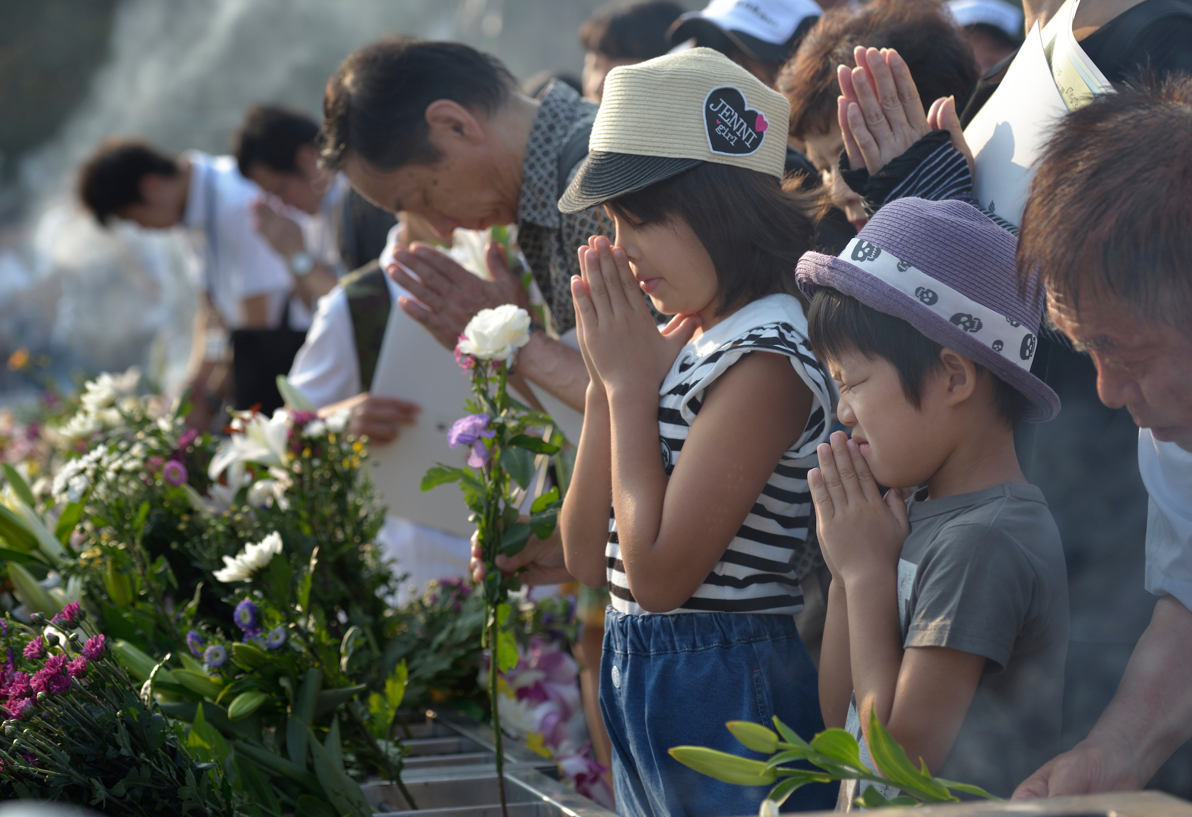 People praying on August 6, 2015, at a memorial in Hiroshima, Japan, that commemorates the victims of the atomic bombing of the city by the United States in 1945. PHOTO: PAUL JEFFREY