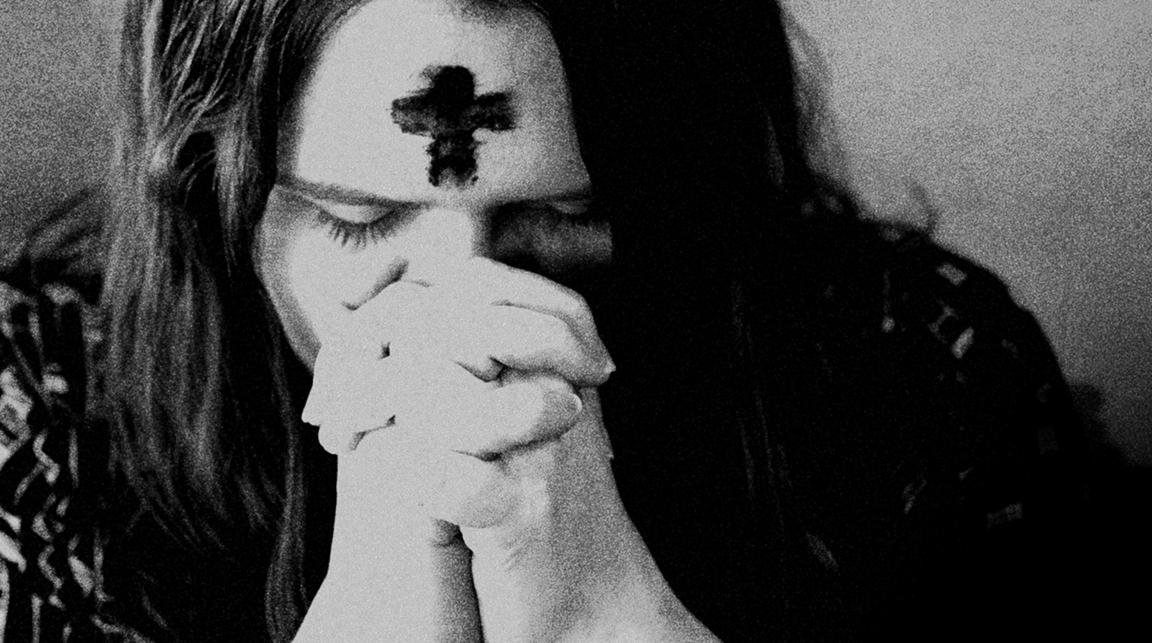 Love involves sacrifice and repentance. A woman prays after having ashes placed on her forehead during an Ash Wednesday service. Image by Kathleen Barry, United Methodist Communications.