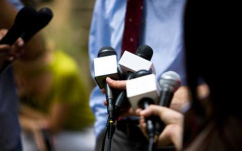 man in blue shirt being interviewed by media with several microphones