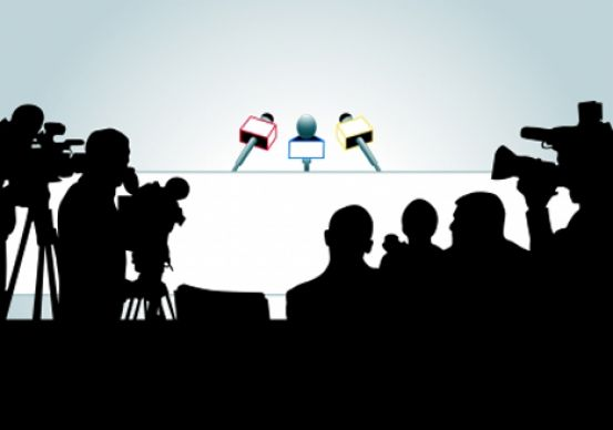 silhouettes of media in front of interview desk with microphones