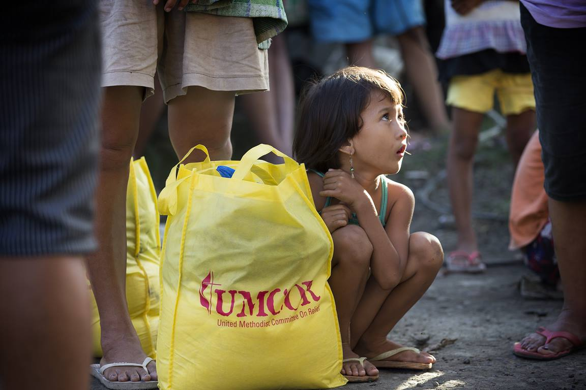 Donna-Grace Orbong, 5, sits with her family's food bag following a distribution by the United Methodist Committee on Relief for survivors of Typhoon Haiyan in Tacloban, Philippines. Photo by Mike DuBose, UMNS