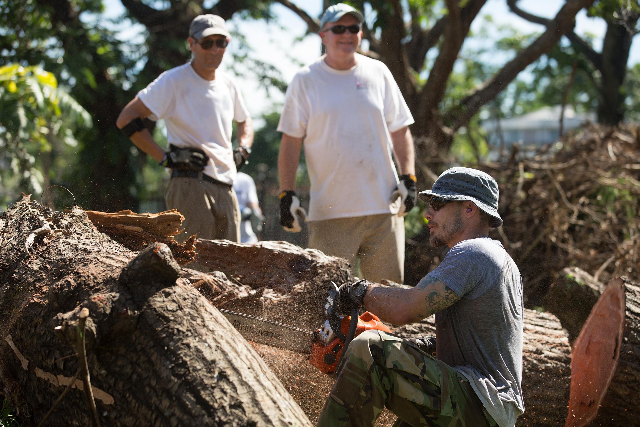 Un hombre corta un árbol después de huracán maría en San Juan, Puerto Rico. Foto cortesía de Mike DuBose.