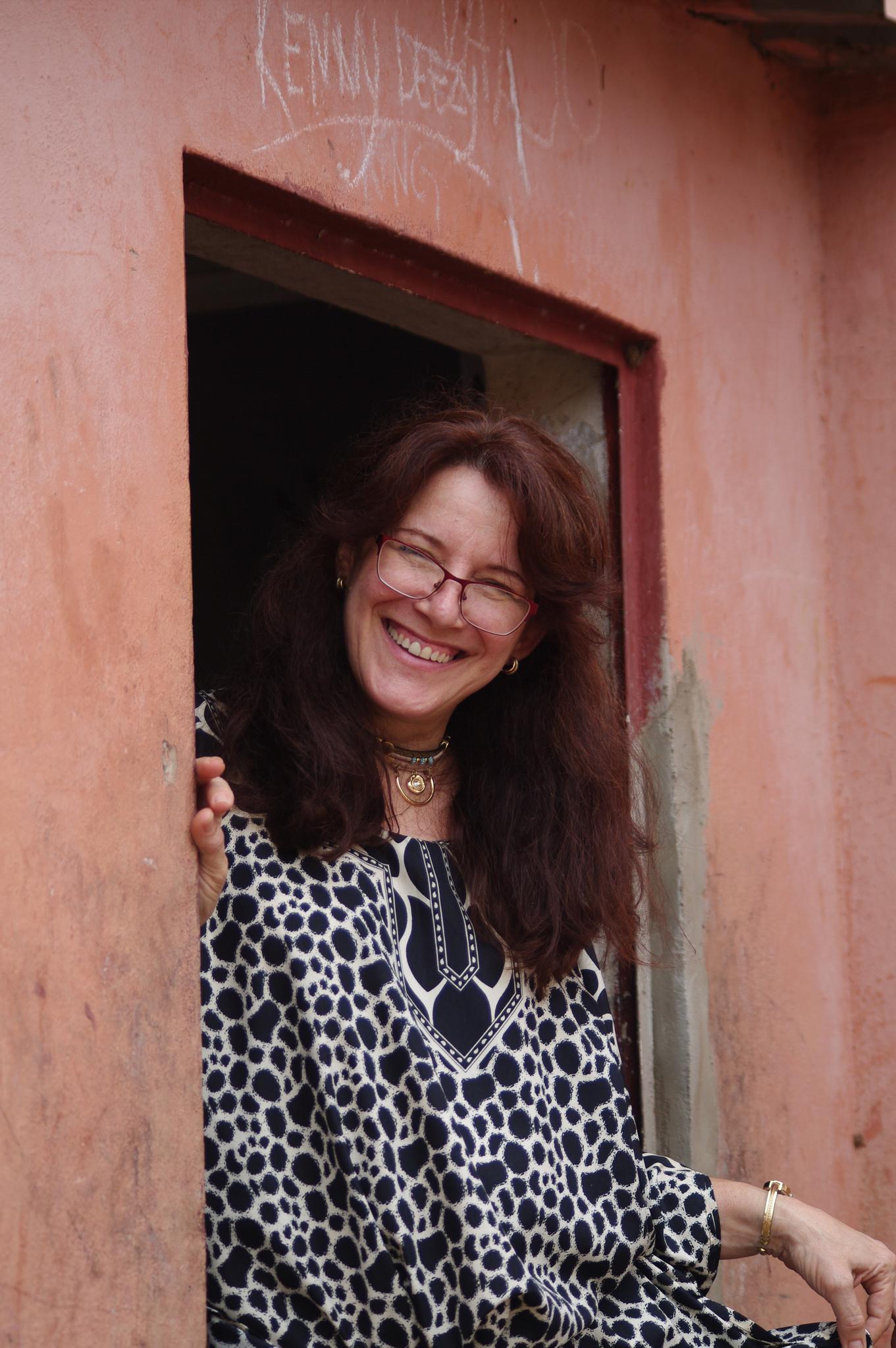 Mujer sonriente se para en una puerta. Foto cortesía de Gustavo Vazquez.