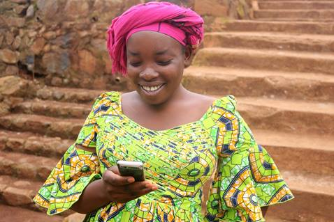 Gracia Wakusomba, a pregnant mother of three, reads a text reminding her of an upcoming appointment at the United Methodist Health Center in Irambo, Democratic Republic of Congo. The hospital works in partnership with central conference communicators to relay the messages. Photo by Philippe Kituka Lolonga, UMNS.