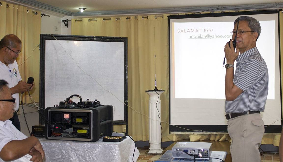 The Rev. Jose Umali (right) tries ham radio equipment during a lecture to clergy and laity in the Philippines. Photo courtesy of Gladys Mangiduyos