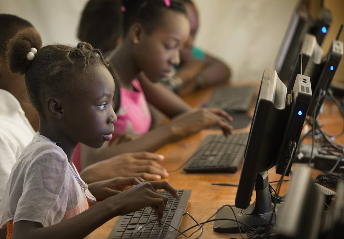 Angeline, 12, works in the computer lab at the Thomas Food Project in Thomas, Haiti. She says she wants to use the computer to write and do research.