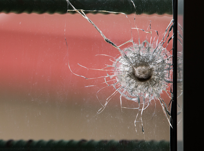 A bullet hole in a newsroom window at The Voice of Hope serves as a reminder of election-related violence in 2011. The station remained on the air during the crisis and several staffers took shelter there.