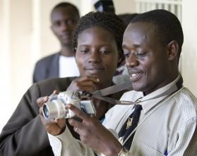 John Barasa Makokha from Kenya (right) and Grace Nakajje from Uganda learn to use a new digital camera during a training session for communicators from the United Methodist Church's East Africa Conference held at Kyambogo University in Kampala, Uganda. A 2007 file photo by Mike DuBose, UMNS.