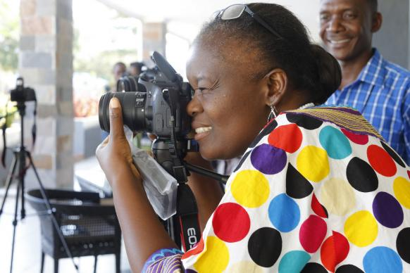 Photo by Kathleen Barry, UMNS  Betty Kazadi Musau focuses her camera during training for communicators from the Congo Central Conference. United Methodist Communications held the training Nov. 12-17 in Ndola, Zambia.