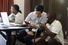 Danny Mai (center) helps Isaac Kunda Muke with a question during the training for Congolese church communicators. Mai and Shelia Mayfield (far left) were part of the team from United Methodist Communications, which held the training. Photo by Kathleen Barry, UMNS
