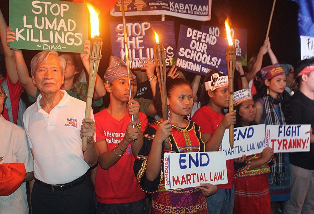 """Participants hold signs during an interfaith gathering at Rajah Sulayman plaza in Manila. Satur Ocampo (left), a well-known social activist, commended the interfaith initiative, calling it """"a signal that society should not remain silent in the face of such exigencies."""" Photo by Gladys Mangiduyo, UMNS."""