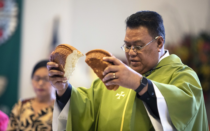 The Rev. Tevita Ofahengaue breaks the Communion bread during a service that features both the English and Tongan languages. In the background is Christiana Uesi.