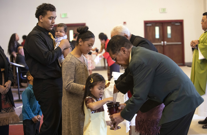Sekope Fainu (left) and other Tongan youth receive Communion.