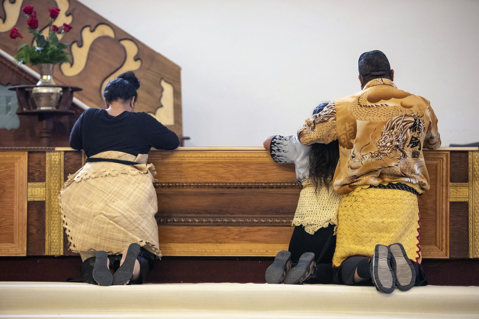 Afu Molisi Jr. prays with his family after receiving communion. Like many in the congregation, he wears the traditional dress featuring the kie kie waist tie as a sign of respect.