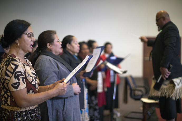 Christiana Uesi (left) sings with others in the adult choir. Uesi is studying to be a certified lay minister and emphasizes that the future of the church is in bilingual services.