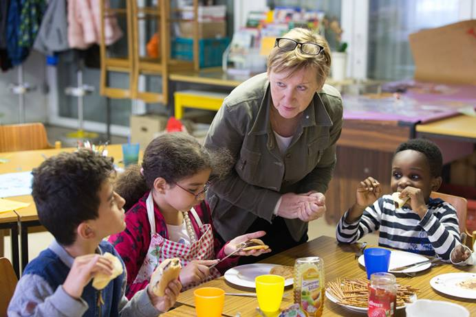 Volunteer Hannah Guzinski helps serve a meal to immigrant children in an educational enrichment program at the United Methodist Peace Church in Hamburg, Germany. Photo by Mike DuBose, UMNS.