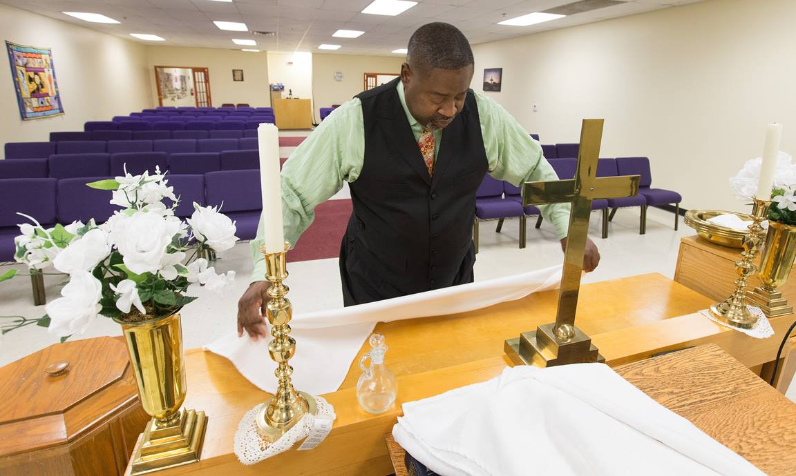 The Rev. Mark Windley prepares the altar for worship at Amazing Grace Community of Faith in Louisville, Ky. Photo by Mike DuBose, UMNS.