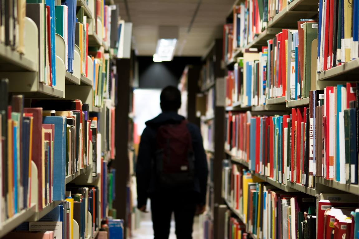 Student walking through library stacks. Photo by Banter Snaps, Unsplash.com.