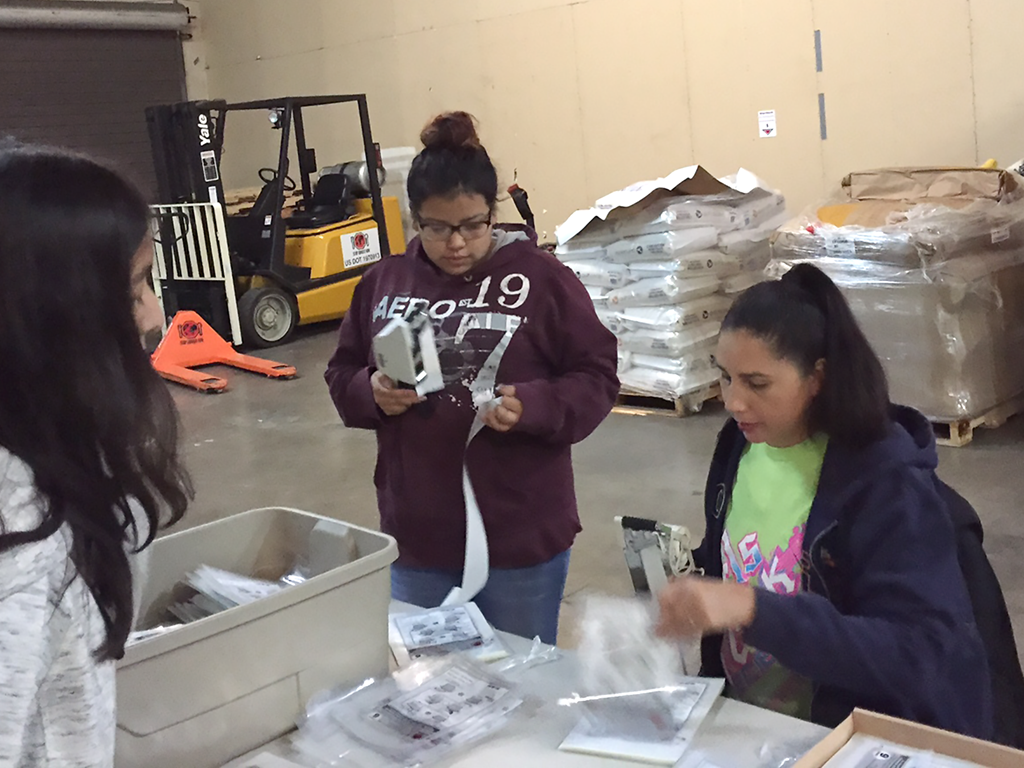 Lynnetta Eyachabbe assists teen girls as they pack meals during a project to fight hunger. Photo courtesy of Jason and Lynnetta Eyacchabe.
