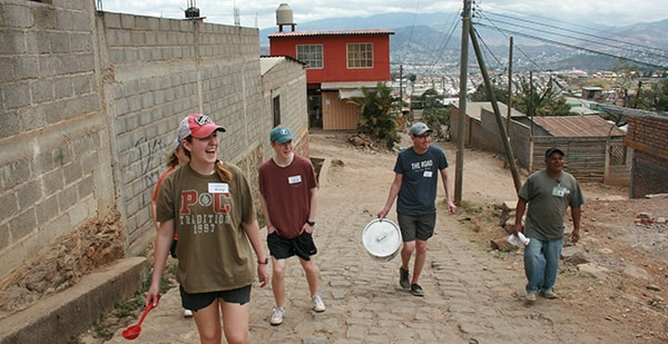 student missionaries carrying bucket