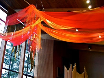 Using red fabric draped above the congregation can create a dramatic symbol of Pentecost in worship.