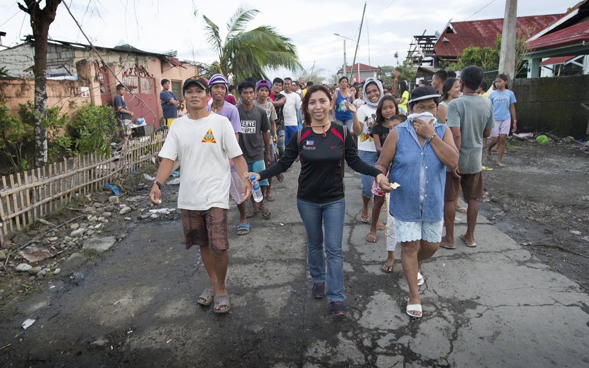 Ciony Ayo-Eduarte (center) leads survivors of Typhoon Haiyan to a food distribution by the United Methodist Committee on Relief in Tacloban, Philippines. Ayo-Eduarte is manager for UMCOR in the Philippines. Photo by Mike DuBose, UMNS