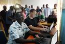 The Rev. John Pena Auta (foreground), provost of Banyan Theological Seminary, works on a computer in the new communications center in Jalingo, Nigeria. Seated next to him is Dan Krause, top staff executive of United Methodist Communications in Nashville, Tenn. In the background are Tafadzwa Mudambanuki (left) from United Methodist Communications and Bishop John Wesley Yohanna of the Nigeria Episcopal Area. Photo by Danny Mai, United Methodist Communications.