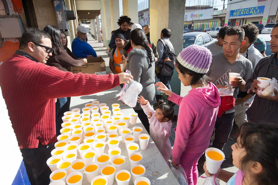 Hector Rodolfo Solorio Castillo (left) of La Gran Comision Methodist Church in Mexicali, Mexico, hands out hygiene kits to migrant families receiving a meal at El Divino Redentor Methodist Church in Mexicali. While UMCOR cannot distribute them to children in the U.S government-run holding facilities, since March the agency has delivered 46,128 hygiene kits to six church-run transitional shelters along the U.S-Mexico border. Photo by Mike DuBose, UMNS.