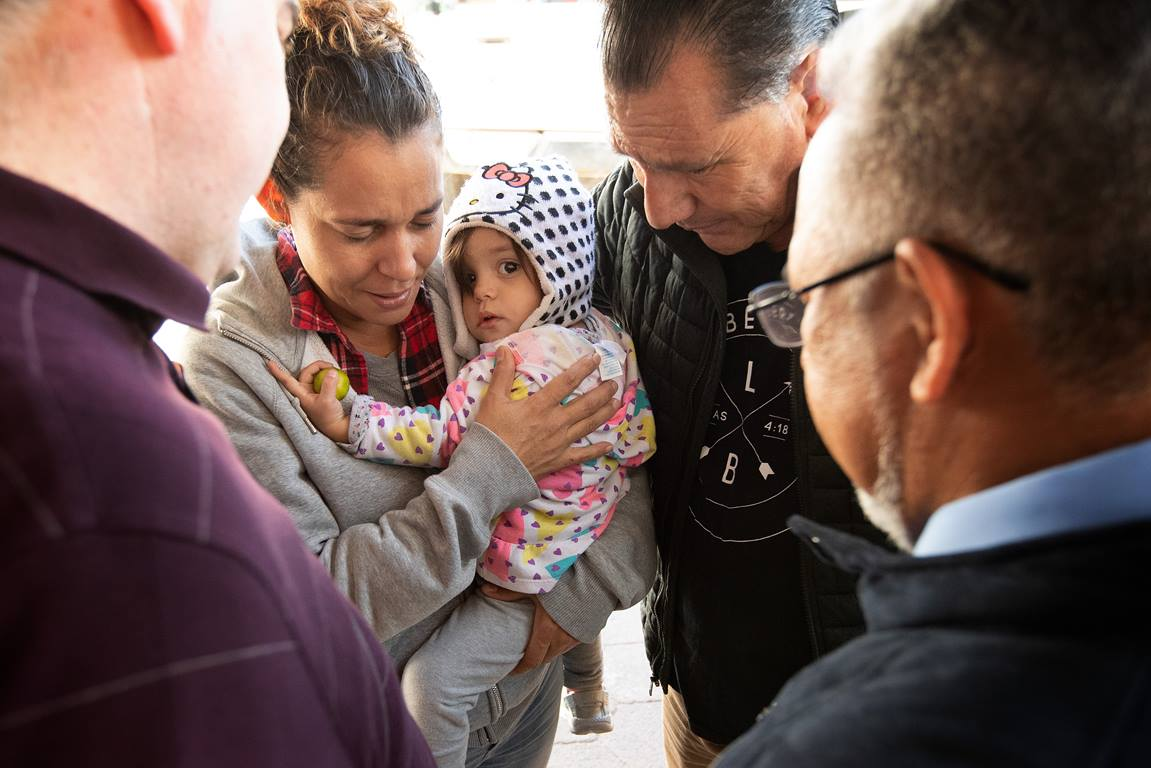 The Rev. Arturo Gonzélez Sandouzl (second from right) and other members of the United Methodist Immigration Task Force pray with Isabél and her 16-month-old daughter Kassandra at a makeshift camp near the bridge leading to the U.S. in Matamoros, Mexico. The mother and daughter traveled from Nicaragua in hopes of seeking asylum in the U.S. Photo by Mike DuBose, UMNS.