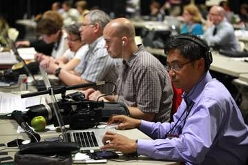 (From right) David Valera, Patrick Scriven, Greg Nelson, the Rev. Karen Nelson and Linda Rhodes work in the newsroom at the 2012 United Methodist General Conference in Tampa, Fla. A UMNS photo by Kathleen Barry.