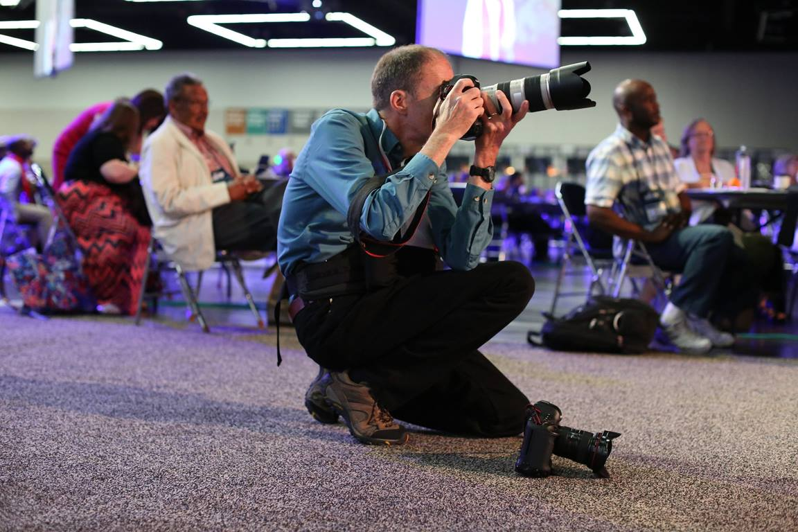 Mike DuBose, photographer with United Methodist News Service, captures moments in the plenary hall during the 2016 United Methodist General Conference in Portland, Ore. Photo by Kathleen Barry, United Methodist Communications.
