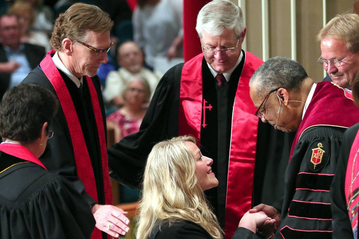 The Rev. Tiffany Nagel Monroe (center) rises with the help of Bishop Robert E. Hayes Jr. after she was ordained elder in the Oklahoma Conference June 1, 2016, at St. Luke's United Methodist Church in Oklahoma City. Monroe and her father, Alan Nagel, both were ordained elder during the service, having graduated in the same class at Saint Paul School of Theology. Photo by Hugh W. Scott, Oklahoma Conference.