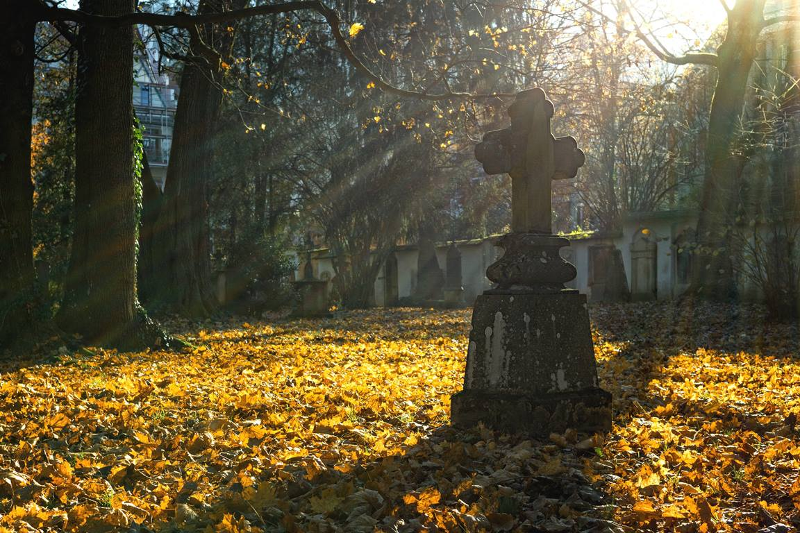 Autumn light streams past a cross monument in a cemetery. Image by Pexels, courtesy of Pixabay.