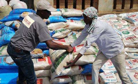 Jean Tshomba, coordinator of UMCOR's disaster management office in Eastern Congo, hands over a bag of flour to one of the beneficiaries during the distribution of food in the Lubutu ecclesiastical district at the end of November 2019. The United Methodist Committee on Relief provided humanitarian assistance to war-displaced people in the region. Photo courtesy of UMCOR Disaster Management Office, East Congo.
