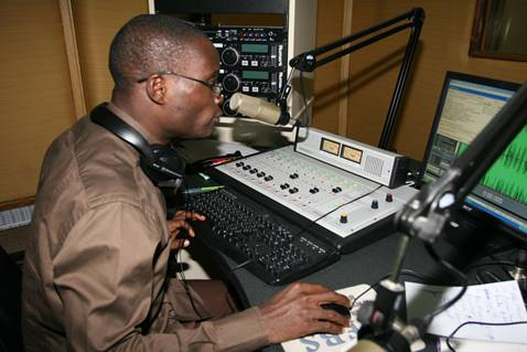 Joachim Gnatin Diahi monitors an afternoon broadcast at 101.6 FM Abidjan. Diahi is an anchor, producer and technician at the station.