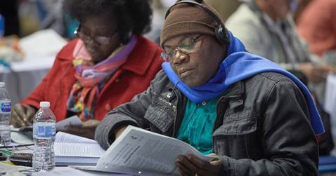 A delegate studies a printed version of proposed legislation before a February 26, 2019, vote to strengthen denominational policies about homosexuality. Photo by Paul Jeffrey, UM News.