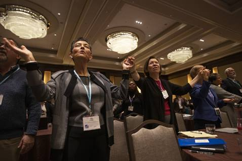 Kim Simpson, chair, Commission on General Conference, and Janice Griffith, Illinois Great Rivers, join hands in prayer during opening worship at the 2020 United Methodist Pre-General Conference held in Nashville, Tenn. Photo by Kathleen Barry, UM News.