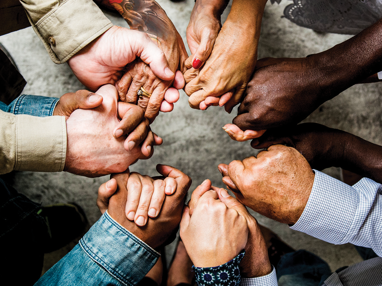 A diverse group of people stand in a circle holding hands. Image by Rawpixel, iStockphoto.com.