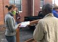 Camille Cody (left), a volunteer with Centenary Community Ministries Inc. in Macon, Ga., looks over paperwork while talking with a man about the U.S. government's stimulus check program. Volunteers have to date helped more than 50 homeless and poor people fill out the complicated tax forms and applications required to receive a check. Photo courtesy of Centenary Community Ministries Facebook page.