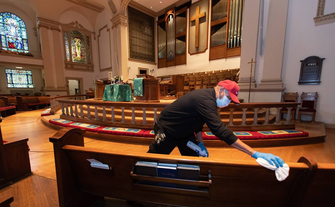 Custodian James Jimmerson disinfects pews to prevent any possible spread of the coronavirus at Belmont United Methodist Church in Nashville, Tenn., on Sunday, May 10, 2020, following online worship, which is recorded in the sanctuary. Photo by Mike DuBose, UMNews