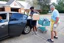 David Idikwu, left, and Phil Slicker load groceries into the car of a client at The Shepherd's Market, a ministry of St. John's United Methodist Church in Baton Rouge, La. Idikwu and Slicker, members of the church, volunteer at the twice-weekly food pantry. Photo by the Rev. Lane Cotton Winn.