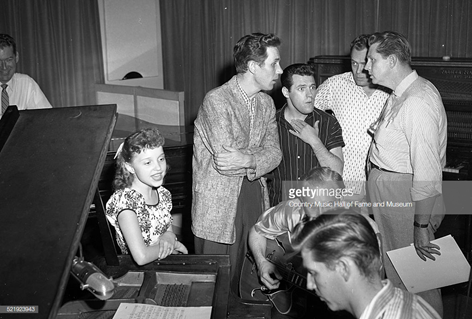RCA artist Libby Horne recording session at Television, Radio, and Film Commission of the Methodist Church, (TRAFCO), Nashville, 1955 - 1957. RCA then rented this studio and office space from the Methodist Church. L-R: KWTO announcer Joe Slattery, Horne, Chet Atkins, Foggy River Boys member Charlie Hodge (hand on chest), guitarist Homer Haynes, pianist Floyd Cramer in foreground, Foggy River Boys members Earl Taylor and Monty Matthews. Photo by Elmer Williams/Country Music Hall of Fame and Museum/Getty Images.
